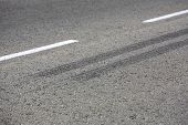 stock photo of tar  - Close up view of rubber tyre tracks on a tar road from vehicles braking harshly - JPG