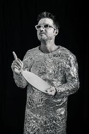 image of spaceman  - Portrait of spaceman holding UFO flying saucer and pointing up - JPG