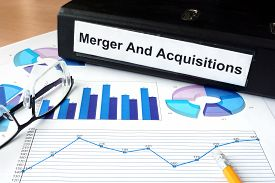 stock photo of merge  - File folder with Merger and Acquisition and financial graphs - JPG