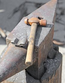 stock photo of blacksmith shop  - Anvil and sturdy hammer in the workshop of the blacksmith - JPG