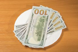 image of stewardship  - notes of dollars on a white plate on a wooden table - JPG