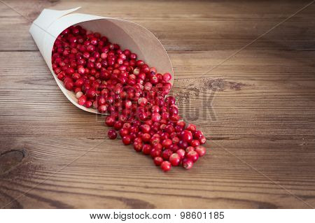 Many bright red cowberries in a paper bag