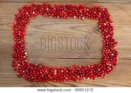 Frame with red berries cowberries on a wooden background