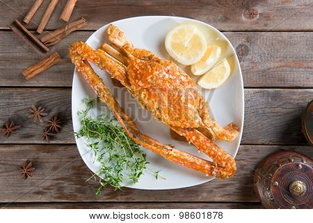 Top view cooked delicious hot and spicy sauce blue crab on white plate with herb ingredients, at wood background. Fresh cook with hot smoke steams.