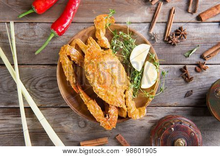 Above view cooked delicious hot and spicy sauce blue crab and ingredients, on wooden background. Fresh cook with hot smoke steams.