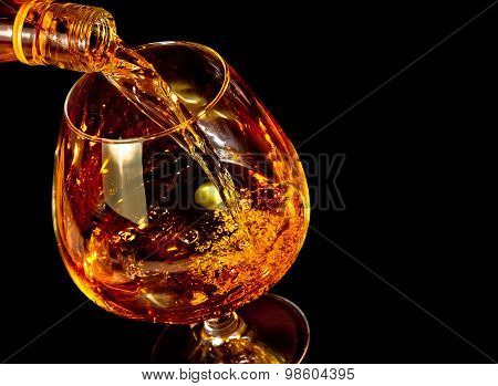 Barman Pouring Snifter Of Brandy In Elegant Typical Cognac Glass On Black Background
