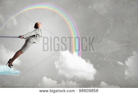 Young businesswoman with ropes on hands trying to fly