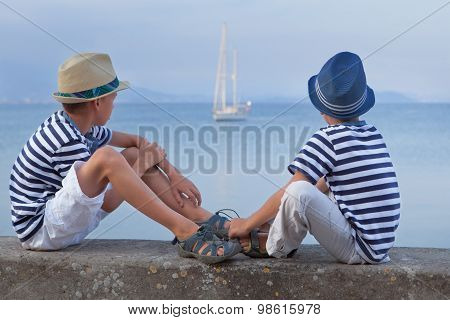 Two Similar Brother Sitting On Waterfront,