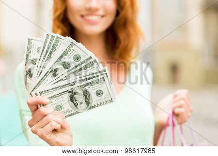 tourism, travel, sale and consumerism concept - close up of happy woman with shopping bags and dollar money on city street