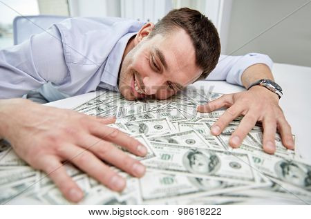 business, people, success and fortune concept - happy businessman with heap of dollar money in office