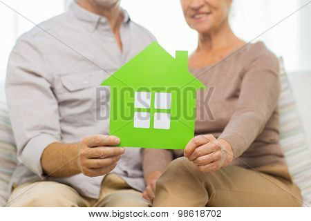 family, relations, real estate, age and people concept - close up of happy senior couple with green paper house cutout at home
