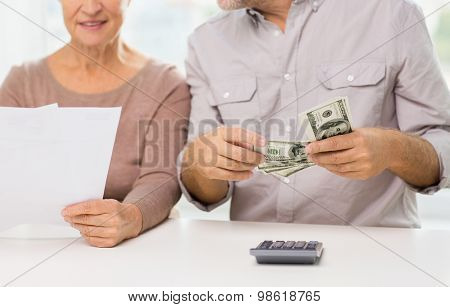 family, business, savings age and people concept - close up of smiling senior couple with bills, dollar money and calculator at home
