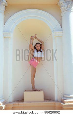 Teen girl dancer posing in arc of ancient building
