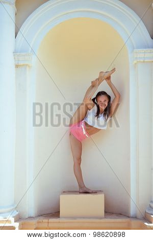Teen girl dancer posing in arc of ancient building, image toned.