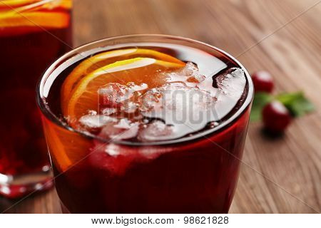 Glasses of cherry juice on wooden table, closeup