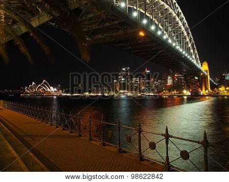 Sydney harbor under the bridge with opera house by night