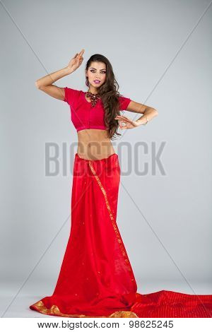 Full body cheerful traditional Asian Indian woman in indian sari, isolated on gray background