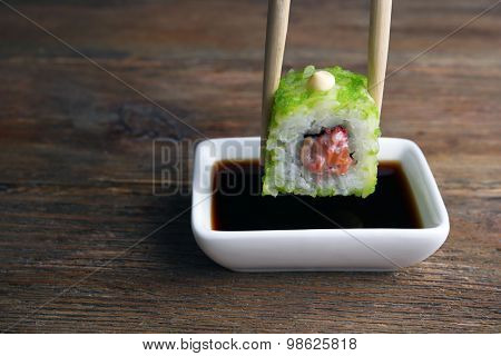 Dipping roll in sauce on wooden table