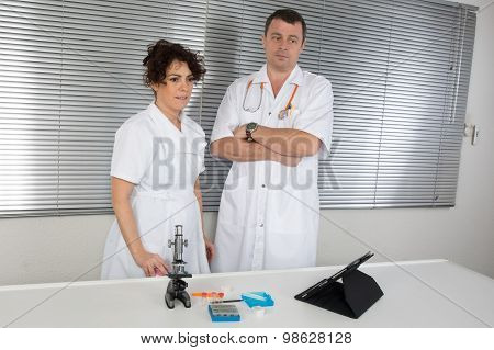 Female Scientist And Her Senior Male Supervisor Pipetting And Microscoping In The Life Science Resea