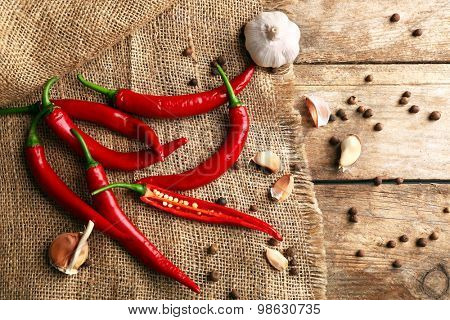 Red hot peppers with spices on table close up