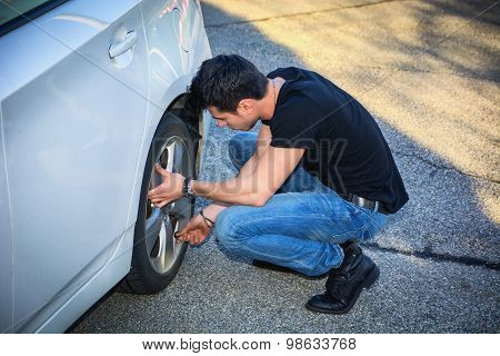 Handsome Young Man Changing Tires of his Car