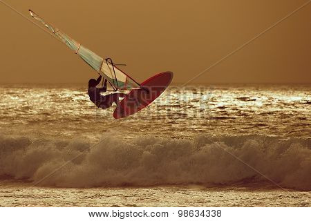 windsurfer jumping in a sunset sky