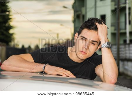 Young man sitting on his car's door, resting on the roof