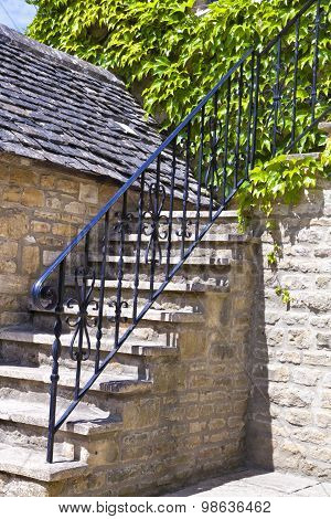 stone stair case in an old cottage with metal railings and wall covered with green vine grape plant