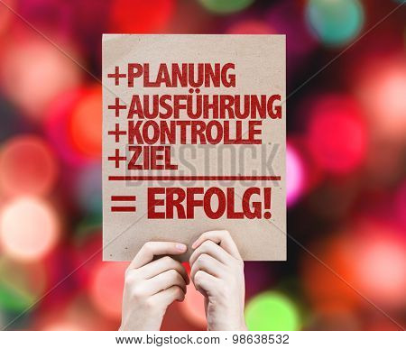 Planning + Execution + Control + Target = Success (in German) card with bokeh background