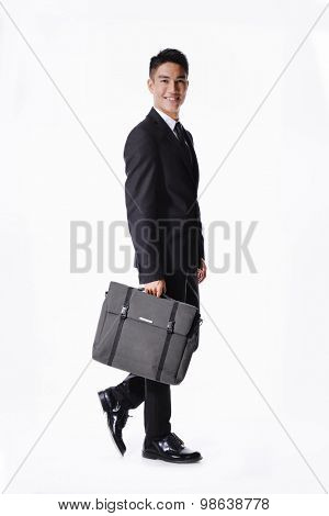 Portrait of a handsome young business man walking carrying a suitcase  full body