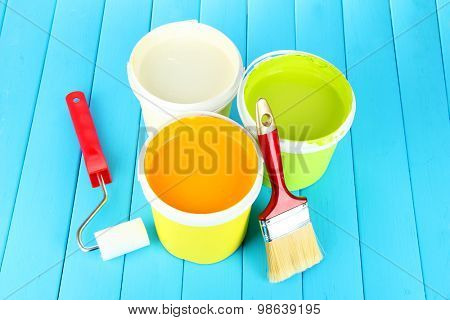 Set for painting: paint pots, brushes, paint-roller on blue wooden table