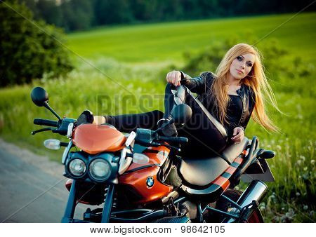 Young sexy woman sitting on red motorcycle