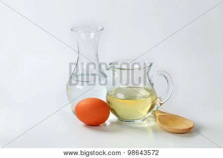 carafe of cold water, jug of sunflower oil, egg and wooden spoon