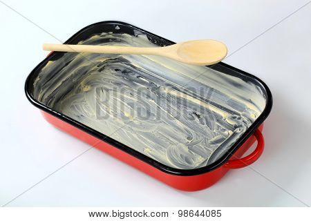 red baking pan greased with butter