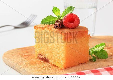 slice of homemade sponge cake on wooden cutting board