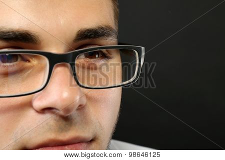 Attractive young man with glasses on gray background