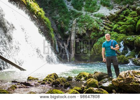 Tourist With Camera Near Waterfall