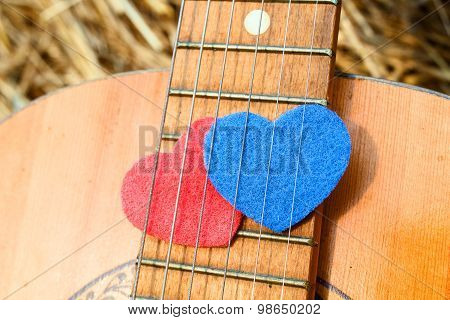 Two Symbols Hearts Together Under The Strings Of The Guitar
