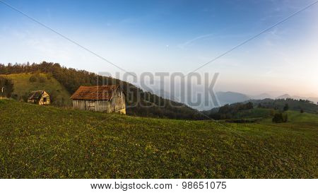 Autumn sunset at hillsides and meadow with mist over Danube river
