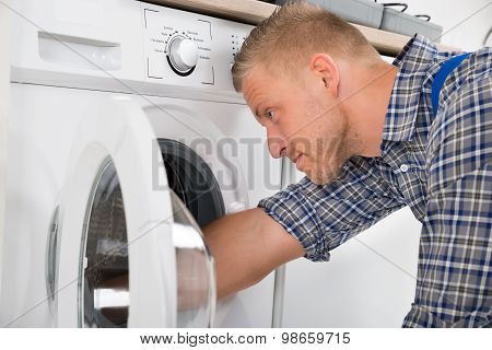 Handyman Repairing Washing Machine