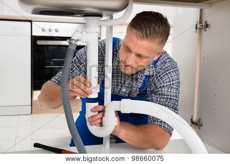 Plumber Repairing Pipe Of Sink
