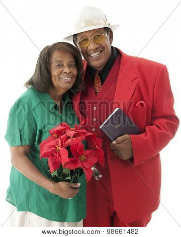 A happy senior couple dressed for Christmas.  She's carrying a pot of red poinsettias.  He's holding his Bible.  On a white background.