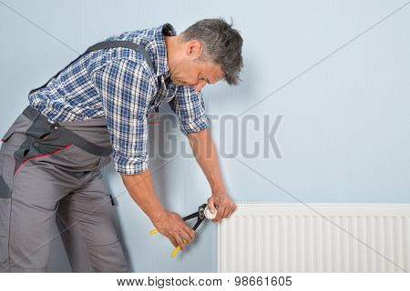 Male Plumber Fixing Radiator