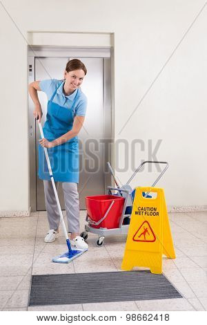 Worker With Cleaning Equipments And Wet Floor Sign