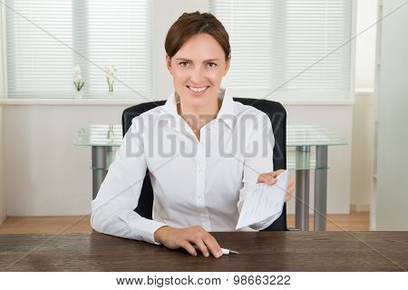 Businesswoman Offering Cheque In Office