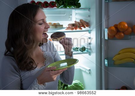 Woman Eating Donut In Front Of Fridge