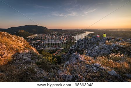 Man And Woman Looking At View Of Small City With River From The Hill At Sunset