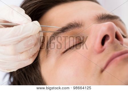 Beautician Hands Plucking Man Eyebrows With Tweezers
