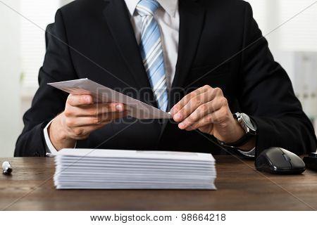 Businessman With Envelopes At Desk