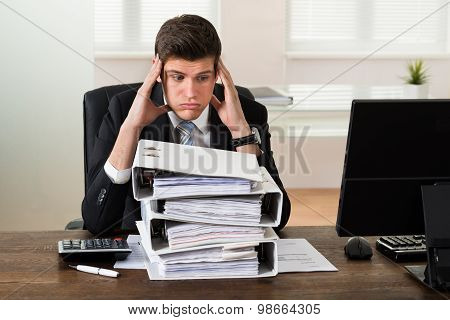 Businessman Looking At Stack Of Folders